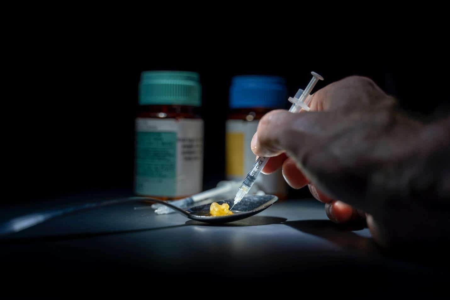 a needle injecting heroin on a spoon as one battles heroin addiction and seeks help at an addiction rehab center